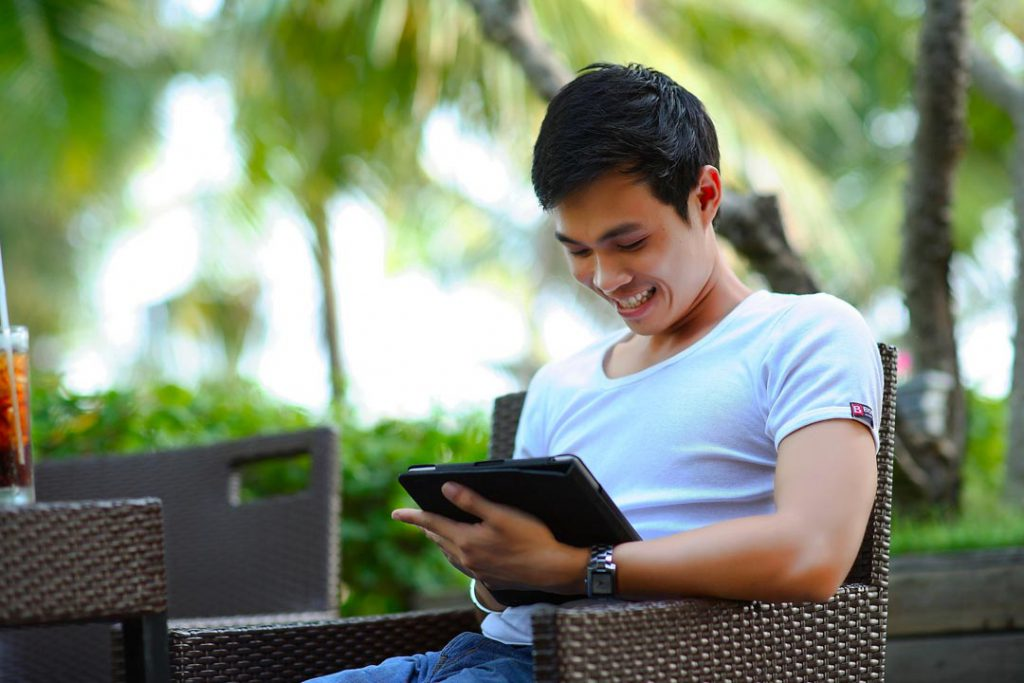 Man smiling at tablet device