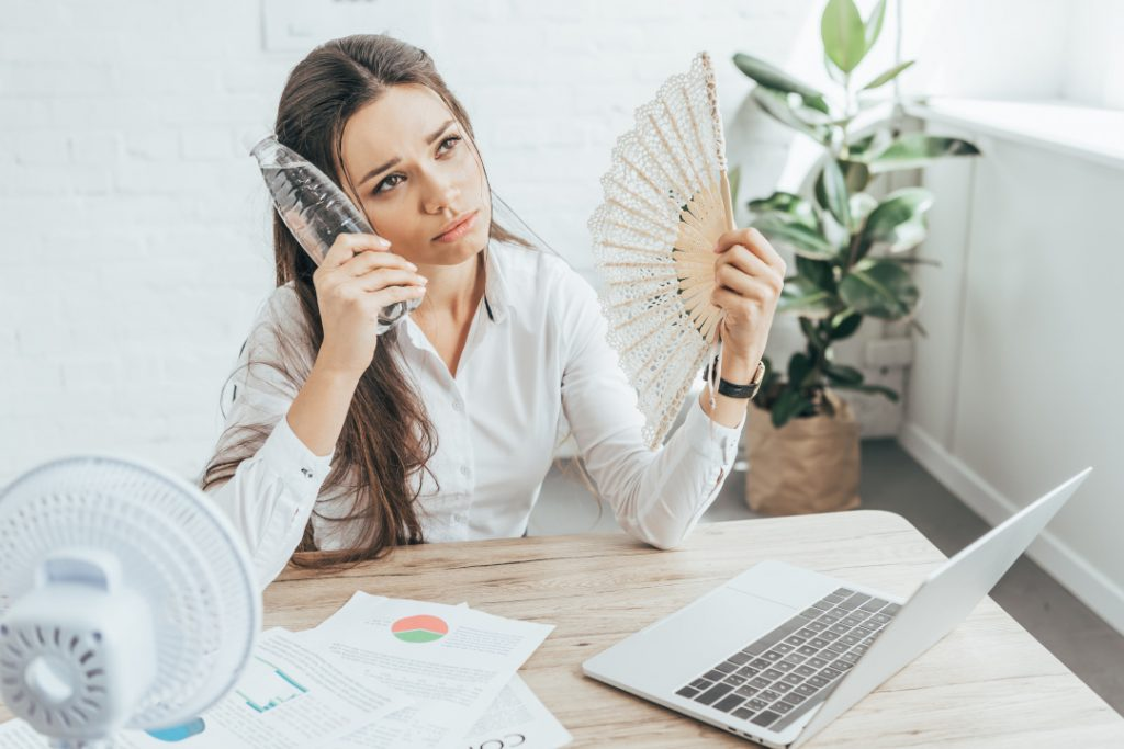 businesswoman cooling herself with electric fan, hand fan and bottle of water at workplace