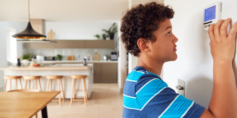 boy changing temperature on central thermostat