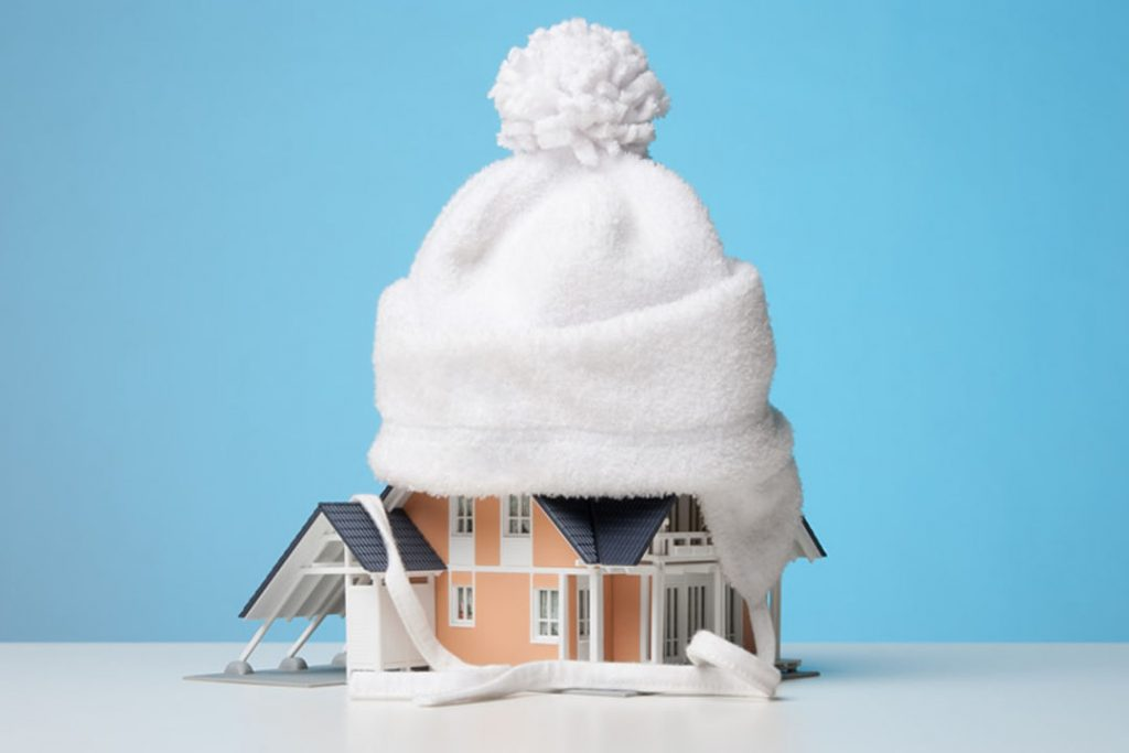 High resolution image of a miniature toy house fittedwith a winter cap on top, on a plain white surface.