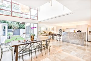 A large dining area, kitchen and living room looking out onto a garden