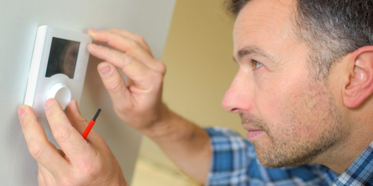A man with a screwdriver inspects a wall-mounted thermostat