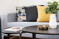 Colorful pillows on couch with table and flower pot