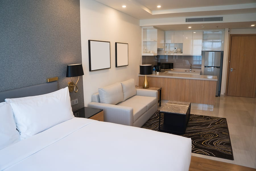 Hotel room interior with bedroom area, living space and kitchen corner
