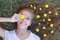 Beautiful young woman lying on lawn with flowers on hair