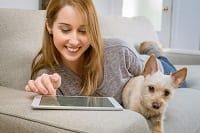 Young woman working on tablet with her dog sitting on sofa